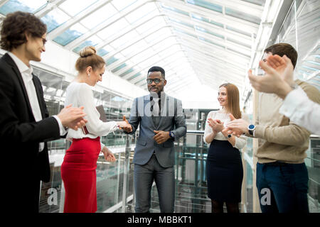 businessmen making agreement, their colleague standing near by - Stock Photo