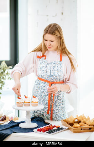 Portrait of pretty young woman cooking cupcakes - Stock Photo