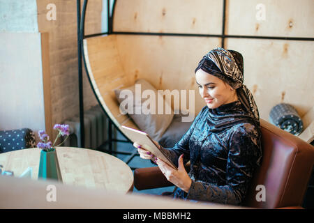 beautiful Arabic Muslim girl using tablet in cafe - Stock Photo