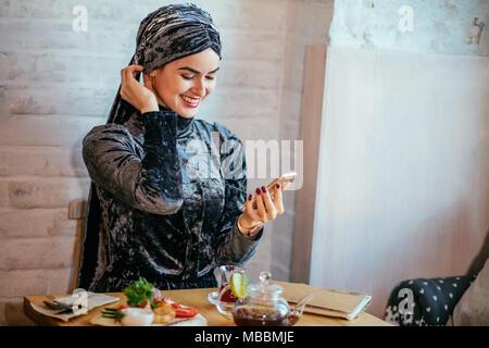 muslim women holding smartphonephone. thinking of good memories. - Stock Photo
