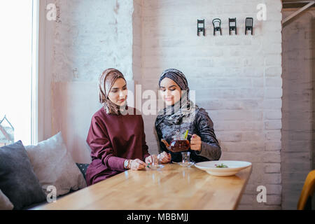 two caucasian muslim woman drinking tea in cafe - Stock Photo