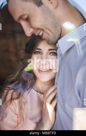 young couple smiling hugging near window - Stock Photo