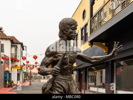 Los Angeles, CA, USA - April 5, 2018: Bruce Lee statue in Central Chinatown. Street scene with red balloon lanterns. Building. Silver sky. - Stock Photo