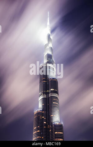 DUBAI, UAE - MAR 23, 2014: Tallest skyscraper of the world called Burj Khalifa during night with motion clouds, Dubai, United Arab Emirates - Stock Photo