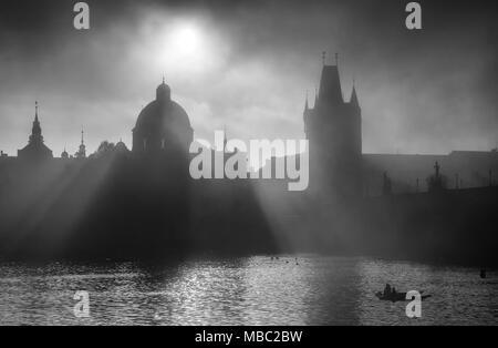 Charles Bridge Towers during foggy sunrise with fisherman, Prague, Czech republic - Stock Photo