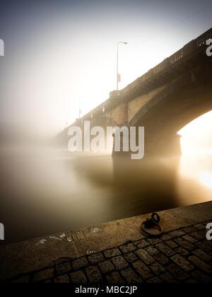 Morning view at Palacky bridge. Historical bridge over Vltava river. Foggy sunlight at riverbank. Typical autumn season. Prague, Czech republic - Stock Photo