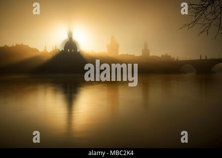 Foggy sunrise view. Detail of St. Francis church at Krizovnicke square. Sunlight over historical building during autumn morning, Prague, Czech republi - Stock Photo