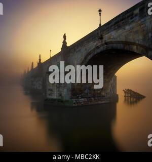 Charles Bridge during sunrise with fog, Prague, Czech republic - Stock Photo