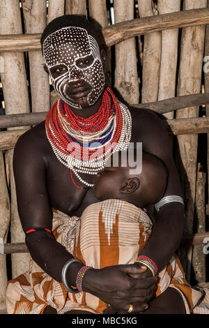 Young woman with painted face and baby, Karo tribe, Southern Nations Nationalities and Peoples' Region, Ethiopia - Stock Photo