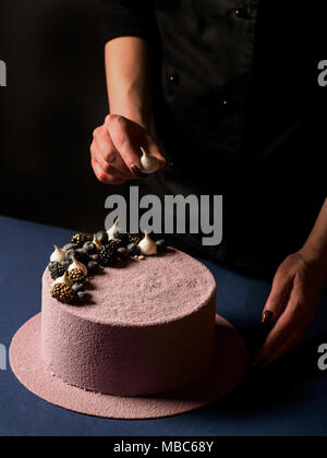 close-up of female hand decorating delicious pink mousse cake with fresh berries on dark background, vertical photo - Stock Photo
