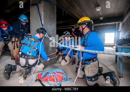 Firefighters from the Mississippi Task Force, Urban Search and Rescue team secure a system of ropes to enable their teammate's escape from a simulated collapsed building during the training exercise PATRIOT South 18, at Camp Shelby, Miss. on Feb. 14, 2018. PATRIOT South, a joint-agency domestic operations training exercise, focuses on natural disaster preparedness for not only National Guard units from across the nation, but also civilian first responders. (Ohio Air National Guard - Stock Photo