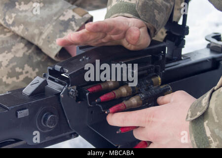 Ukrainian Soldiers assigned to 3rd Battalion, 14th Mechanized Brigade load ammunition into a DshK machine gun at the Yavoriv Combat Training Center here Feb. 16. Currently the 3-14th is completing a training rotation at the CTC where they will be mentored by U.S., Canadian, Lithuanian, Polish, and U.K service members as they strive toward attaining their goal of achieving NATO interoperability. (U.S. Army - Stock Photo