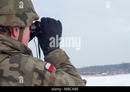 Yavoriv, Ukraine -- A Polish Army Soldier assigned to the Yavoriv Combat Training Center observes DshK machine gun training conducted by Ukrainian Soldiers from 3rd Battalion, 14th Mechanized Brigade, Feb. 16. Currently the 3-14th is completing a training rotation at the CTC where they will be mentored by U.S., Canadian, Lithuanian, Polish, and U.K service members as they strive toward attaining their goal of achieving NATO interoperability. (U.S. Army - Stock Photo