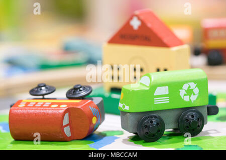 Wooden toy two trains on road with hospital in backdrop (selective focused),Toys for kids indoor playground - Stock Photo