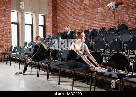 The ballet concept. Young ballerina girls sitting on the black chairs in the hall. Women at the rehearsal in black bodysuits. Prepare a theatrical performance - Stock Photo