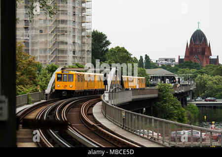An U-Bahn train on the U1 line entering Hallesches Tor station in Berlin, Germany. The Heilig-Kreuz-Kirche is in the background. - Stock Photo
