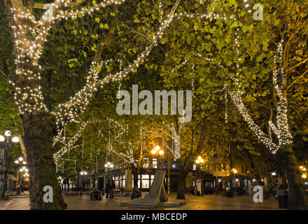 WA15077-00...WASHINGTON -Lights on trees brighten the walking area after dark at the Fireman's Memorial  in Occidental Square in downtown Seattle. - Stock Photo