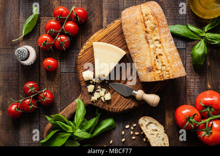 Italian food Parmesan cheese, Ciabatta bread, Bruschetta, Tomatoes and Basil on Rustic Wood Background. Top view - Stock Photo