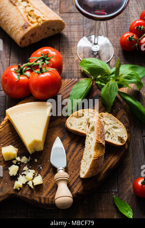 Parmesan cheese, bruschetta, ciabatta bread, tomatoes, glass of wine and basil. Italian food. Table top view - Stock Photo