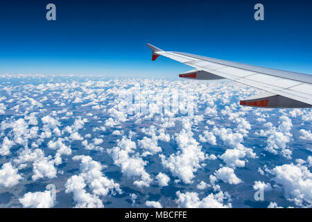 Wing of a commercial airliner flying over fluffy white cumulus clouds, Australia - Stock Photo