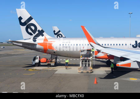 A water truck on the tarmac services a Jetstar Airbus A320 aircraft at Sydney Airport, domestic terminal, Australia - Stock Photo