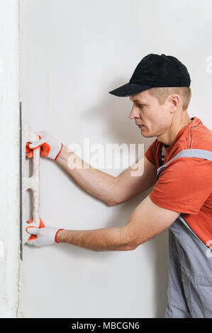 The worker puts f inishing layer of stucco on the wall using a plastering trowel - Stock Photo