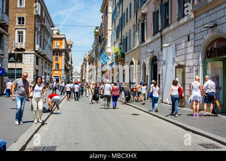 Rome, Italy, june 2015: Romans and tourists strolling along the famous Via del Corso shopping street in Rome on a sunny day in early summer - Stock Photo