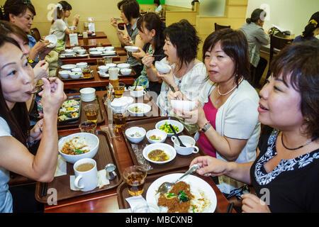 Tokyo Japan Shinjuku Shinjuku NS Building restaurant office workers Asian woman women co-workers eating dining - Stock Photo