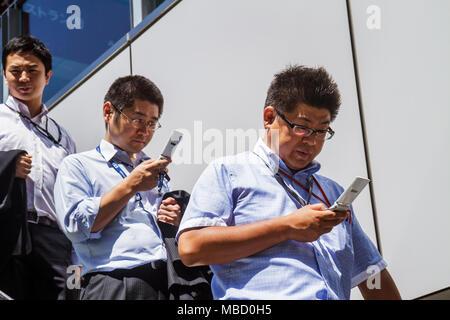 Tokyo Japan Akihabara UDX building Asian man men salaryman mobile cell phone office workers - Stock Photo