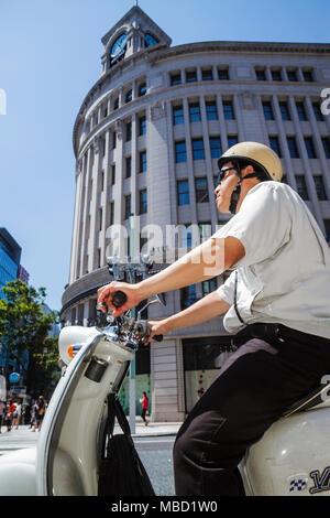 Tokyo Japan Ginza Chuo & Hamuri Dori Street shopping Wako Department Store Asian man motor scooter - Stock Photo