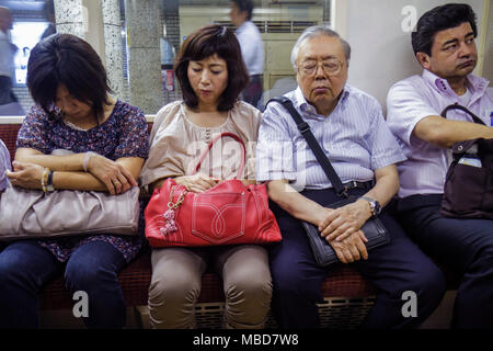 Tokyo Japan Ginza Ginza Metro Station subway train car passengers commuters Asian man woman dozing off nodding falling asleep sl - Stock Photo