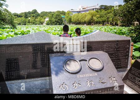 Tokyo Japan Ueno Ueno Park Ueno-koen Shinobazu Pond water lilies flora nature Bentendo Hall shrine memorial man woman couple kan - Stock Photo