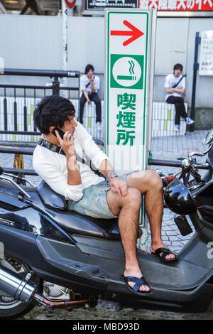 Tokyo Japan Ikebukuro motorcycle kanji hiragana katakana characters symbols Asian man sitting mobile cell phone sign smoking zon - Stock Photo