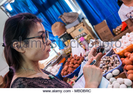 Helen Liu a guide at Cook in Shanghai explaining century eggs (preserved duck eggs) to a group of tourists in a wet market in Shanghai. - Stock Photo