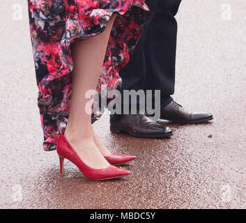 A woman's lower legs, flowery dress and red stiletto heels standing next to a man's legs in trousers and dress shoes on wet  paving - Stock Photo