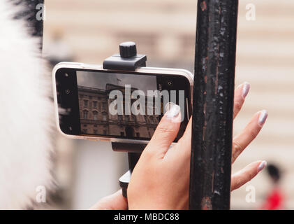 A woman's hand holding a smartphone taking a photograph of Buckingham Palace, London - Stock Photo