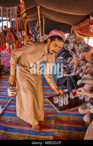 Young bedouin serving tea to the tourists, Wadi Rum Desert, Jordan - Stock Photo