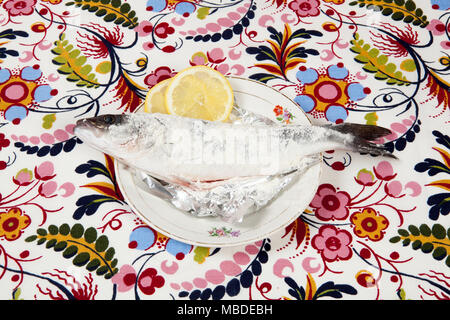 A preparation of a bass fish with a slice of lemon beside inside a flower plate hidden on a flowery fabric. Camouflage game. Minimal color still life  - Stock Photo