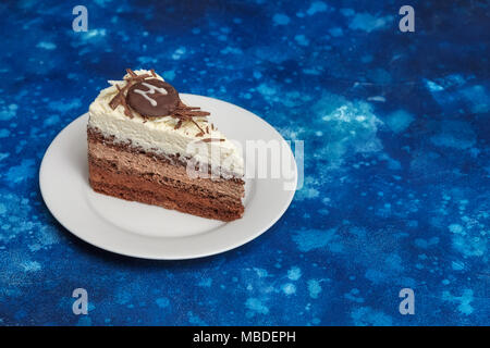 Piece of delicious mousse cake with three different kind of chocolate on white plate. Blue background - Stock Photo