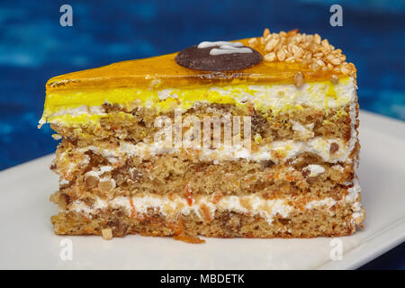 Piece of carrot cake with icing and walnut on white plate, blue background, closeup - Stock Photo