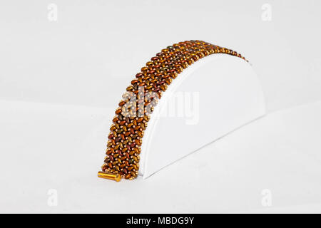a brown and gold hand stitched flat beaded bracelet - Stock Photo