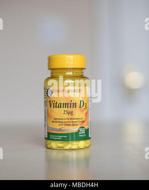Vitamin D supplements in a clear bottle full of little tablets to make you feel better - Stock Photo