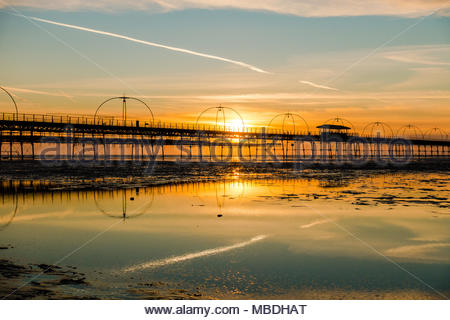 Southport Pier at sunset, showing the meal arches and stays of the bridge at sunset with a jet stream in the sky, which is reflected, England UK - Stock Photo