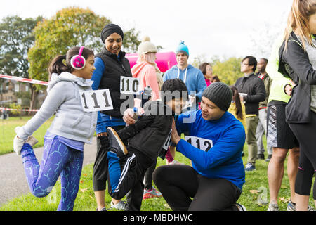 Family runners preparing, stretching at charity run in park - Stock Photo