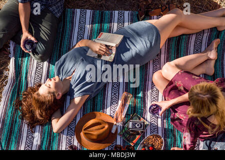 Overhead view young woman with book relaxing on picnic blanket - Stock Photo