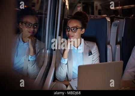Confident, thoughtful businesswoman looking out window on passenger train at night, working at laptop - Stock Photo