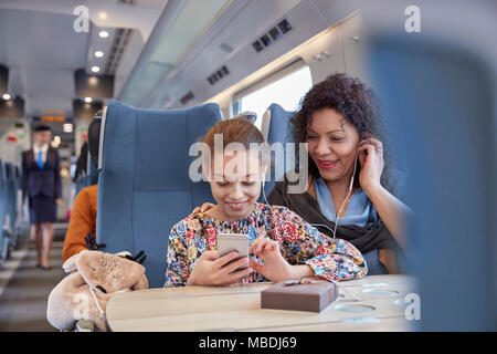 Mother and daughter sharing headphones, listening to music with smart phone on passenger train - Stock Photo