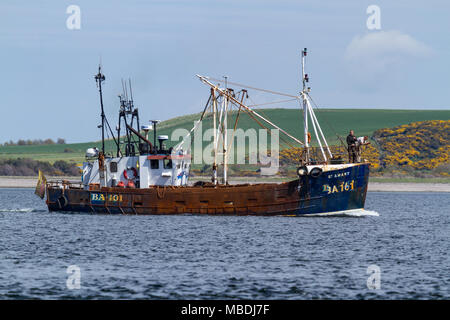 Fishing boat in the Moray Firth heading towards Inverness. Taken from Chanonry Point on the Black Isle, Scotland. - Stock Photo