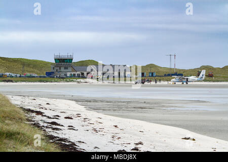 Passengers disembarking from an aeroplane at Barra Airport on the Isle of Barra, Outer Hebrides, Scotland - Stock Photo