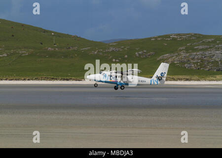 DHC Twin Otter passenger aeroplane taking off from the beach runway at Barra Airport, Isle of Barra, Outer Hebrides, Scotland - Stock Photo
